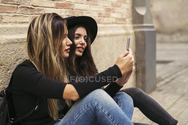 Два лучших друга используют смартфон перед кирпичной стеной — стоковое фото