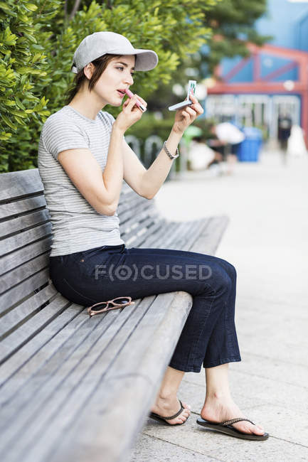 Woman sitting on bench using pocket mirror for applying make up — Stock Photo