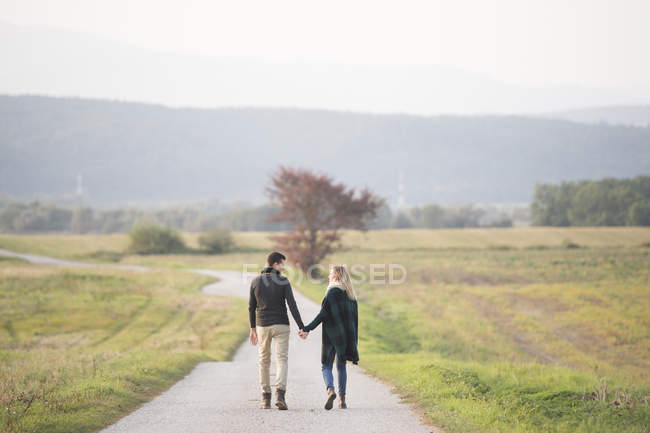 Young couple walking in rural landscape — Stock Photo