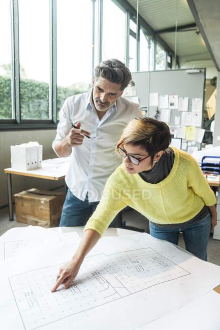 Mâles et femelles architectes discuter le plan au sol dans le Bureau — Photo de stock