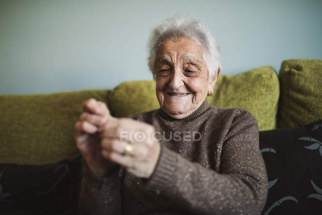 Senior woman passing thread through buttonhole of sewing needle — Stock Photo