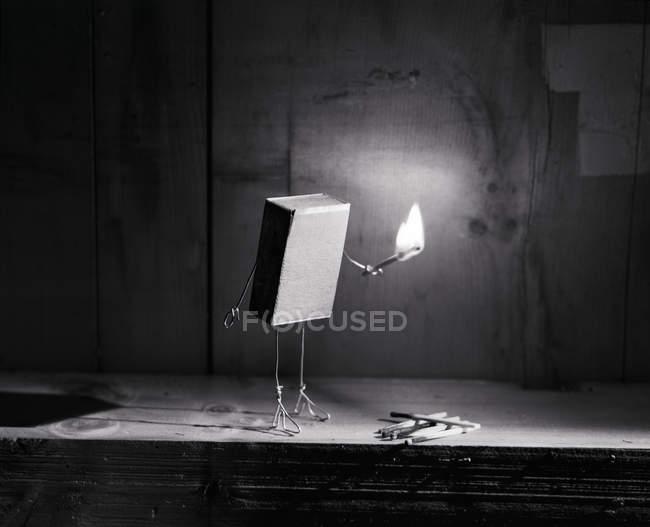 Match box holding burning match — Stock Photo