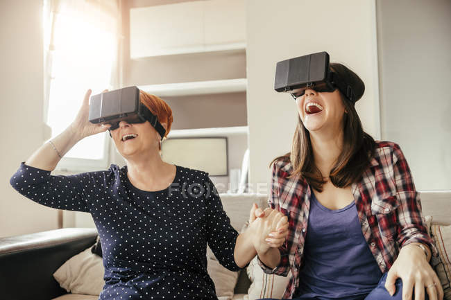 Mother and daughter in glasses of virtual reality sitting on couch — Stock Photo