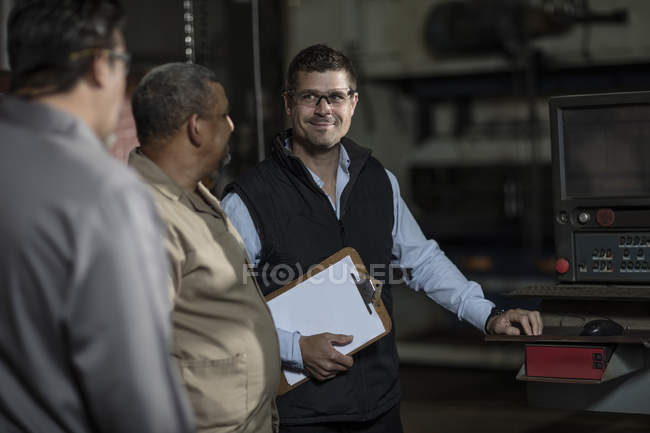 Two male engineers discussing in factory — Stock Photo