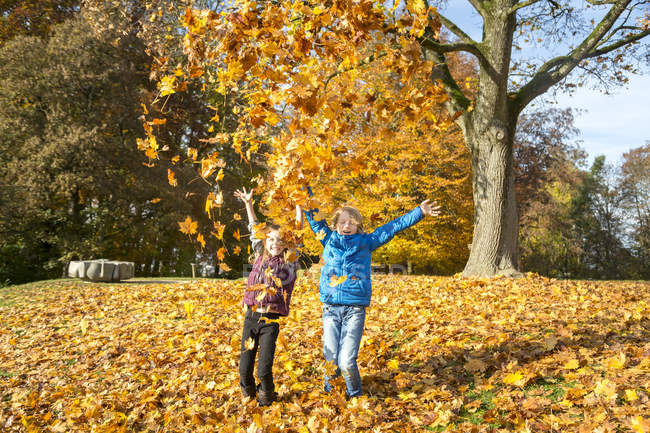 Brother and sister throwing autumn leaves in the air — Stock Photo