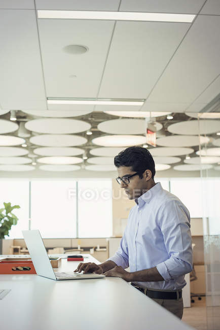Businessman working at high desk with laptop — Stock Photo
