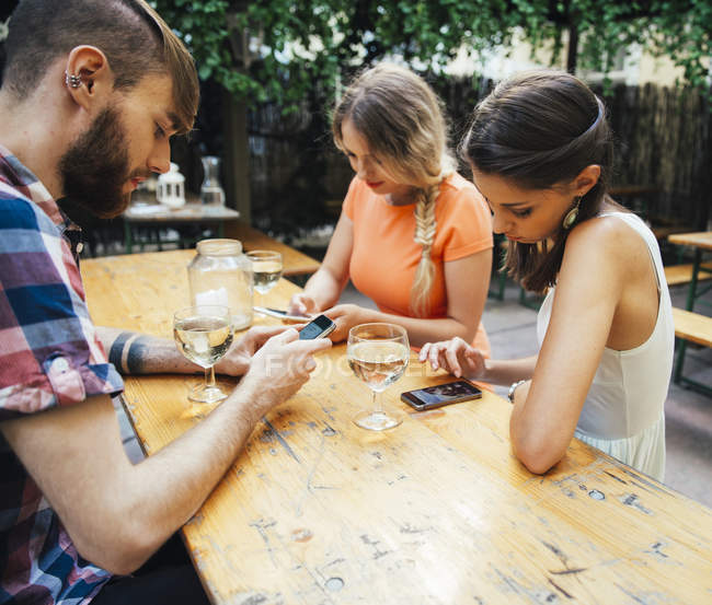 Friends using cell phones and drinking spritzer at outdoor pub — Stock Photo
