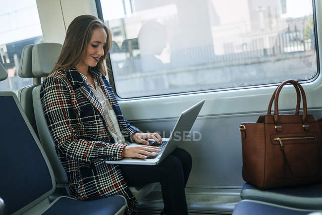 Businesswoman sitting in train and using a laptop — Stock Photo