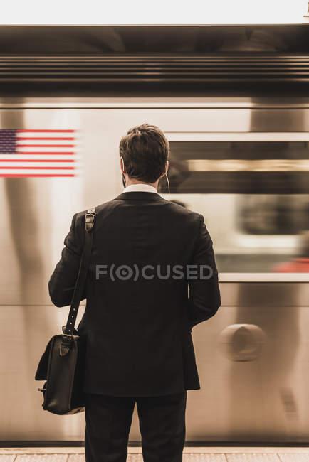 Jovem empresário esperando na plataforma da estação de metro — Fotografia de Stock