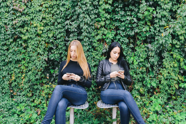 Two young women sitting side by side using their cell phones — Stock Photo