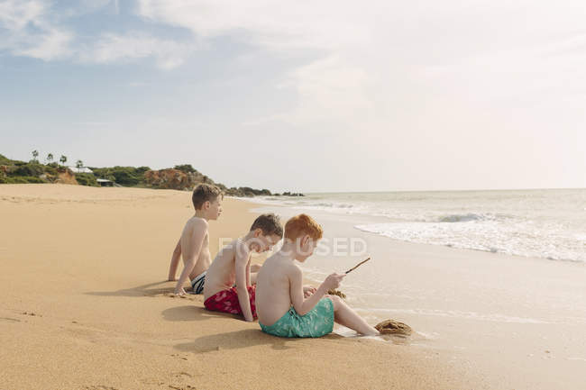 Three boys sitting on the beach at summer vacation — Stock Photo