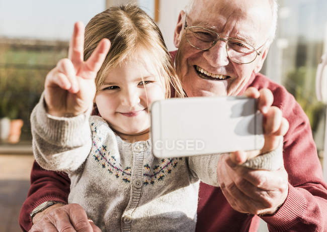 Grandfather and granddaughter taking selfie with a smartphone — Stock Photo