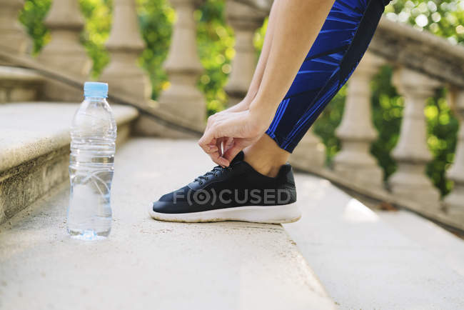 Close-up of shoe and water bottle of sportive woman — Stock Photo