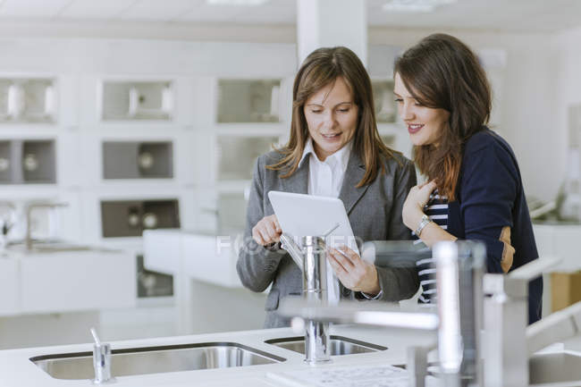 Woman consulting costumer in plumbing shop showing information on digital tablet — Stock Photo
