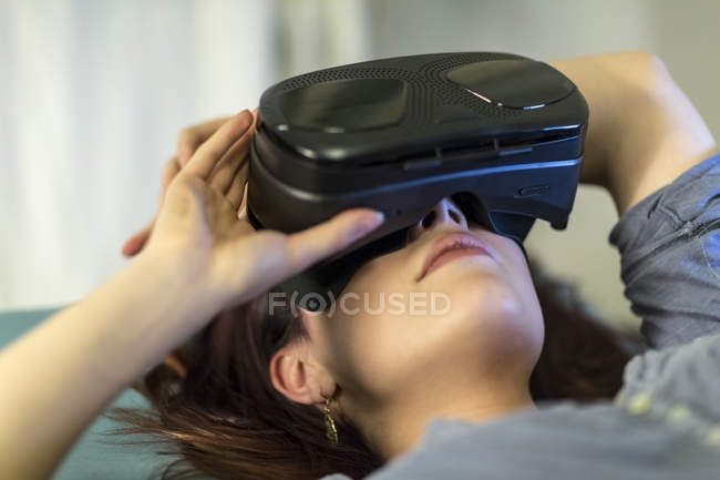 Young woman using Virtual Reality goggles — Stock Photo