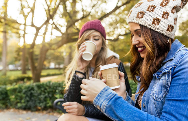 Two best female friends drinking coffee in park in autumn — Stock Photo