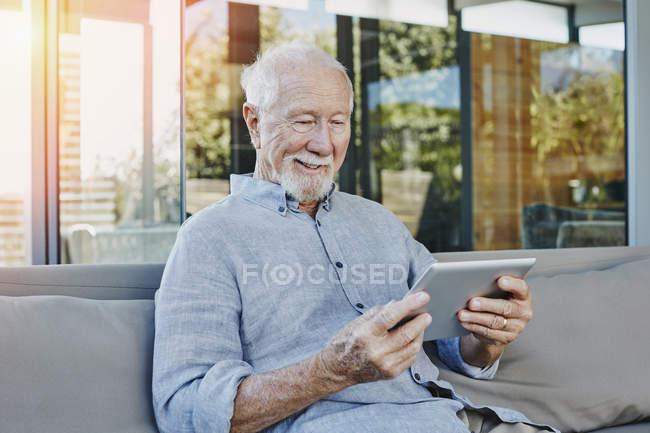 Senior man sitting on terrace reading ebook — Stock Photo