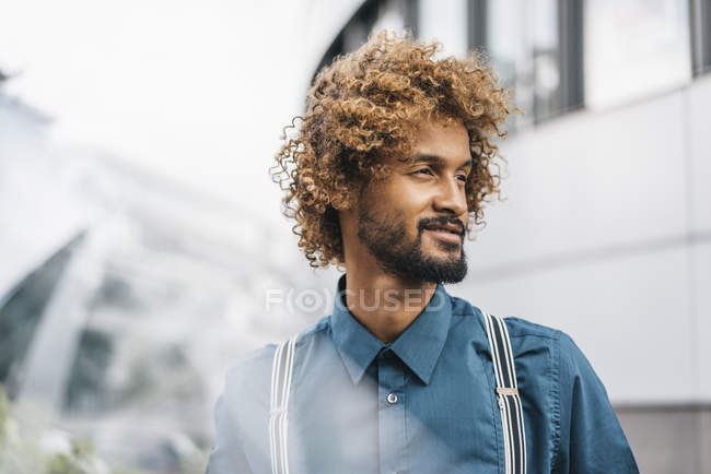 Young man with windswept curls looking away, portrait — Stock Photo
