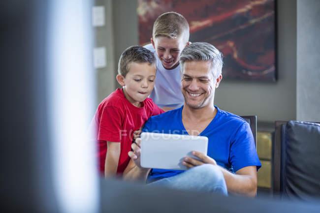 Діти, дивлячись з їх татом на цифровий планшетний — стокове фото