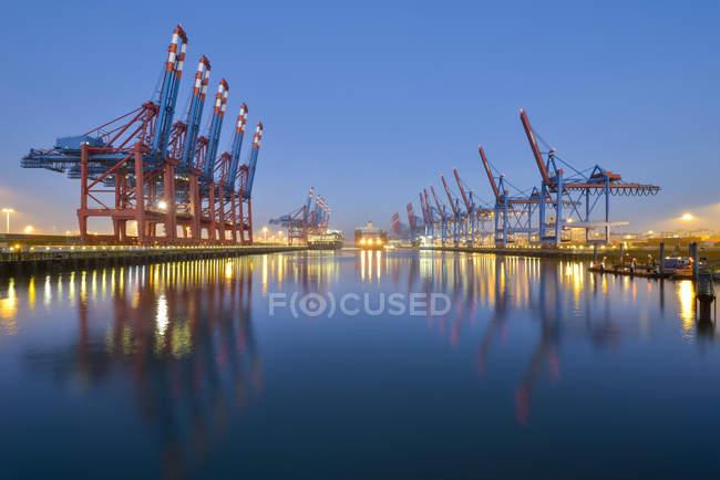 Porto di Amburgo con gru illuminate al tramonto, Germania — Foto stock