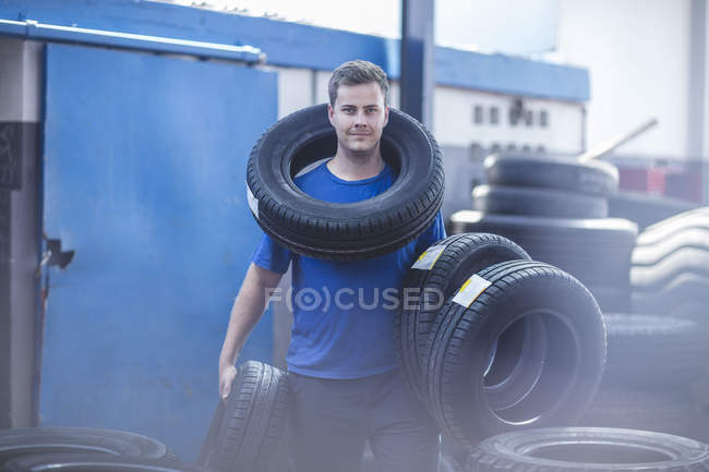 Mechanic holding batch of tyres at workshop — Stock Photo