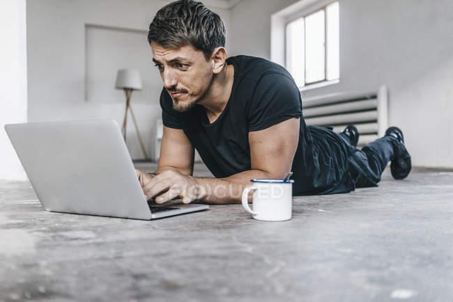 Man lying on floor using laptop in empty loft — Stock Photo