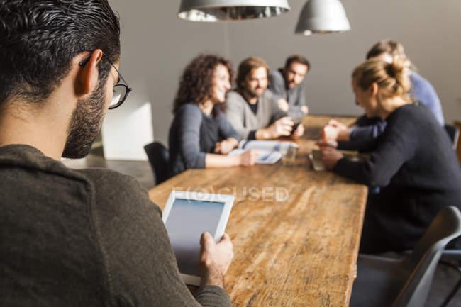 Jovem usando tablet digital no escritório moderno com colegas de trabalho tendo uma reunião em segundo plano — Fotografia de Stock