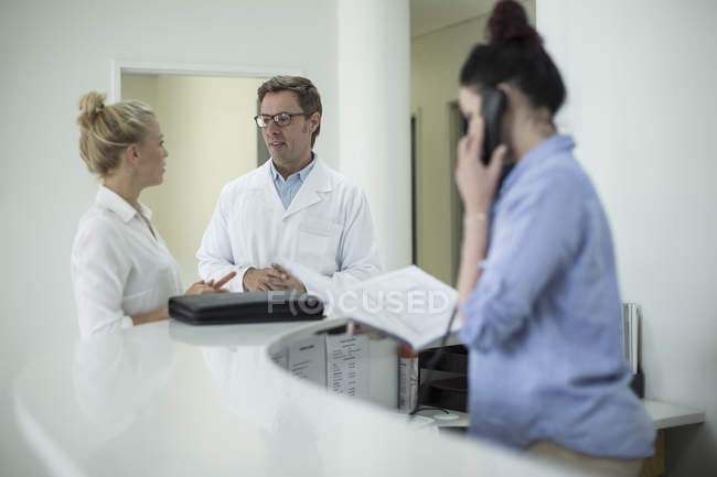 Man and woman in lab coats talking in reception area — Stock Photo