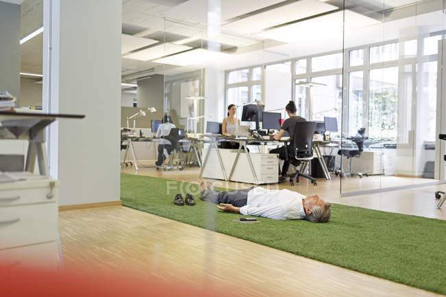 Кавказский бизнесмен лежит на ковре в офисе — стоковое фото