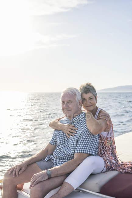 Ласковая пара в лодке обнимает и смотрит на вид — стоковое фото
