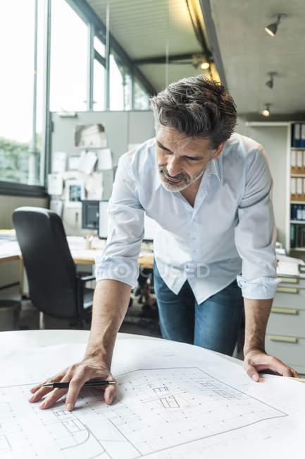 Architecte travaillant sur le plan de terrain dans le bureau — Photo de stock