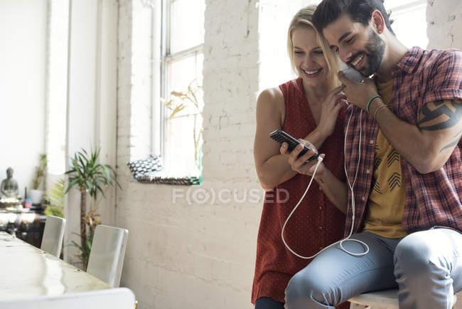Glückliches junges Paar mit Handy am Fenster teilt sich Kopfhörer — Stockfoto