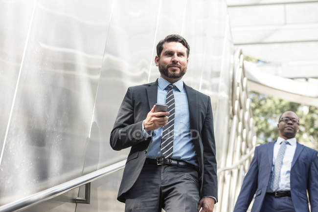 Deux hommes d'affaires confiants marchant à l'extérieur — Photo de stock