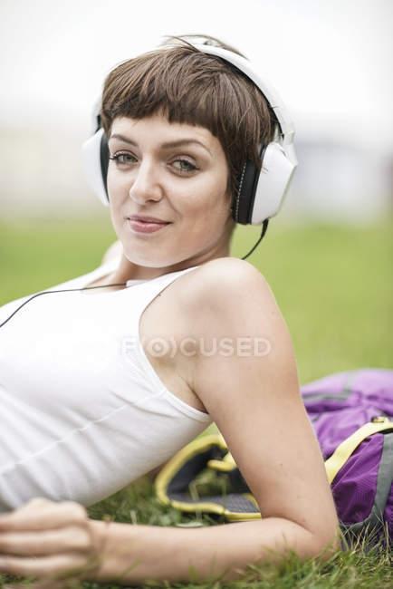 Retrato de uma jovem sorridente deitada no prado e ouvindo música com fones de ouvido — Fotografia de Stock