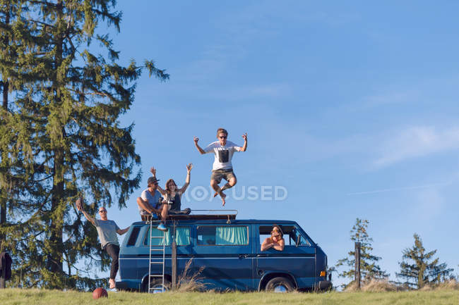 Group of friends having fun at van in nature — Stock Photo