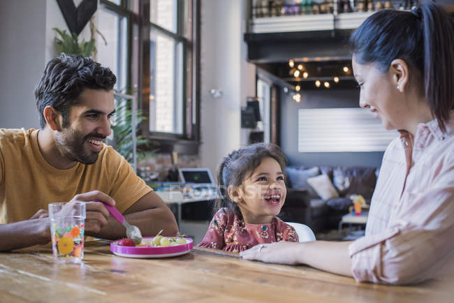 Happy family at table feeding toddler daughter — Stock Photo