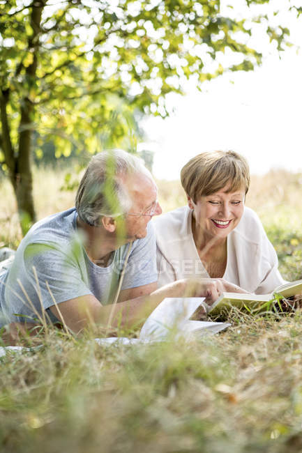 SEnior couple lying outdoors in sunny garden with books — Stock Photo