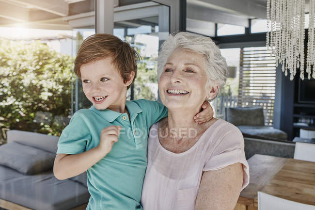 Portrait of smiling senior woman holding grandson — Stock Photo