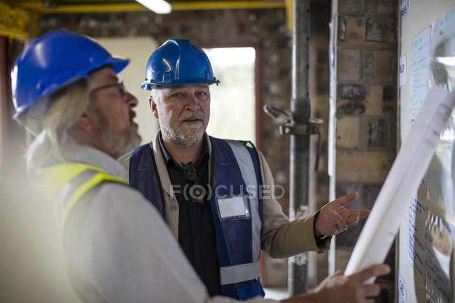 Construction worker and engineer discussing project in site office — Stock Photo
