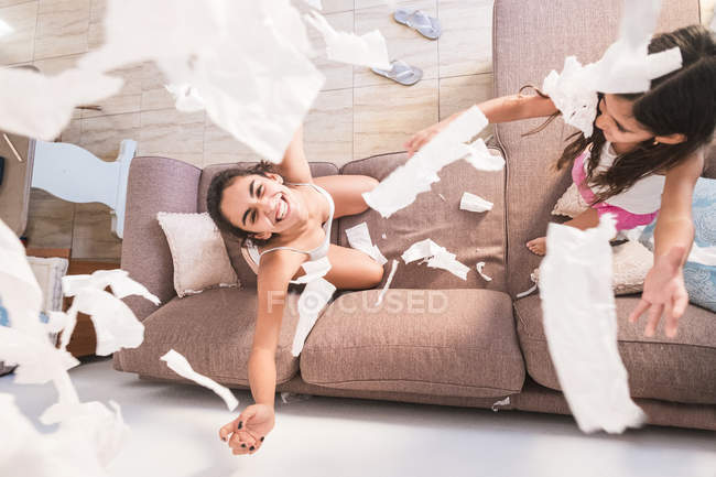Playful teenage girl and her little sister on couch — Stock Photo