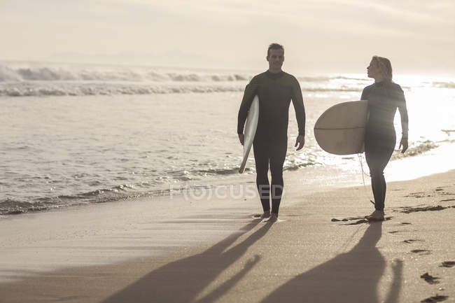 Couple with surfboards walking on the beach — Stock Photo