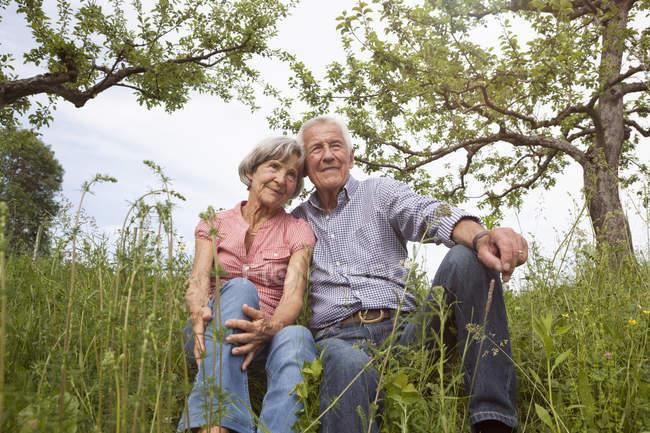 Расслабленная старшая пара, сидящая на лугу — стоковое фото