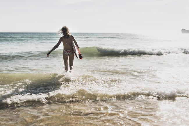Adolescente, caminhando com a prancha no mar — Fotografia de Stock