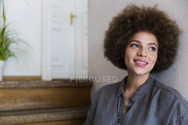 Усміхаючись молоду жінку, що хтось дивитися вбік — стокове фото