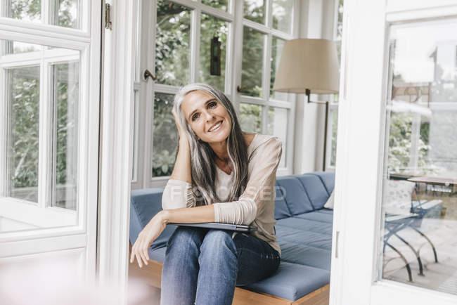 Улыбающаяся женщина сидит в гостиной — стоковое фото
