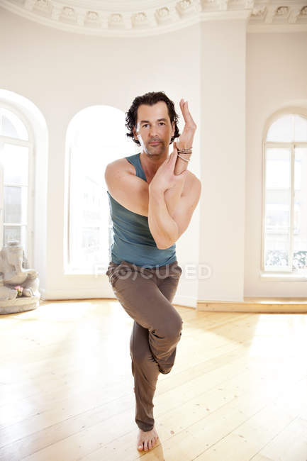Man in sunny yoga studio holding twisted pose — Stock Photo