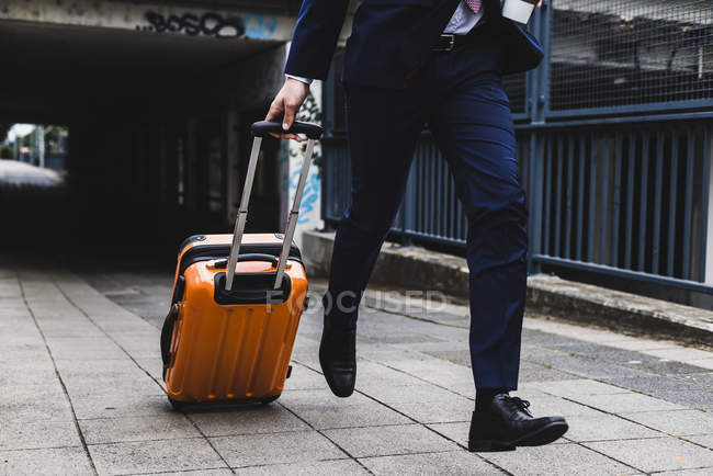 Businessman running with wheeled luggage on business trip — Stock Photo