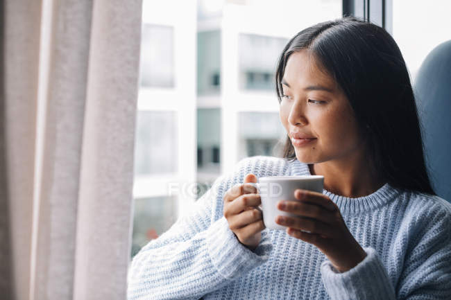 Donna con Coppa in piedi davanti alla finestra — Foto stock