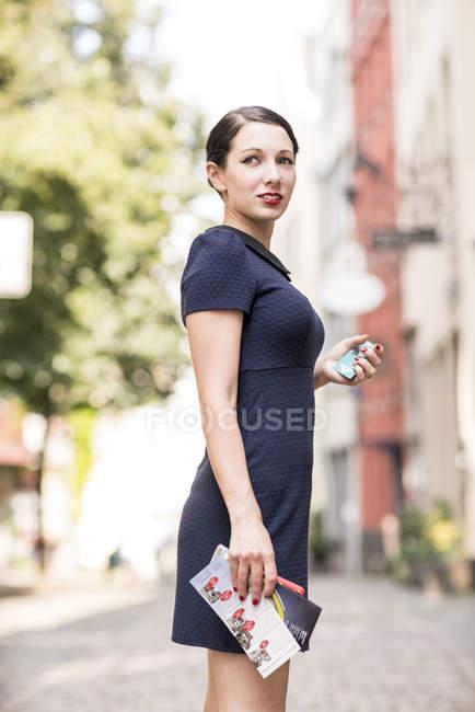 Молода жінка стоїть в місті Озираючись — стокове фото