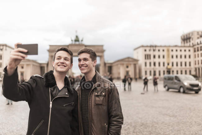 Two teenagers taking a smartphone image of themselves in front of the Brandenburg Gate in Berlin — Stock Photo
